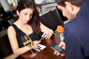 Paar im Restaurant schaut auf ihre Handys
